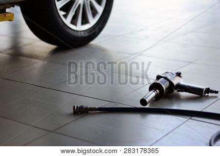 The Metal Wheel With Tire  And Air Wrench With Blue Air Line On Grey Tile At Hte Car Repair Shop