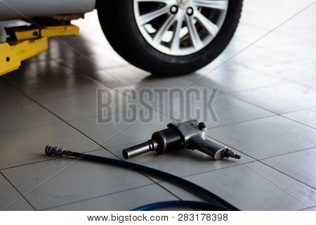 The Bright Light  And  Metal Wheel With Tire  And Air Wrench With Blue Air Line On Grey Tile At Hte