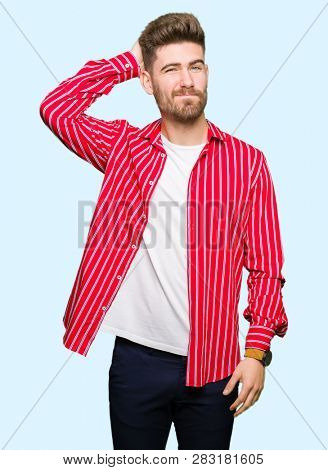 Young handsome man wearing red shirt confuse and wonder about question. Uncertain with doubt, thinking with hand on head. Pensive concept.