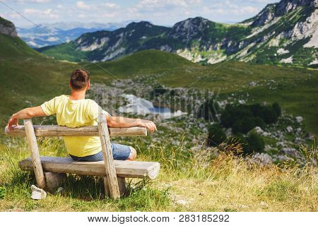 Traveler Mountains Rest Bench. Young Man Mountains Sitting On Wooden Bench. Hot Summer Day While Tra
