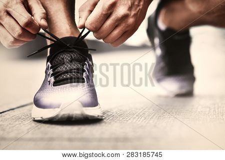 Cropped Image Of Hands Tying Shoelaces On Sneaker, Running Surface Background. Hands Of Sportsman Wi