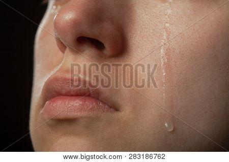 Sad Woman Cries, Shot A Close Up Of Female Cheek With A Tear Drop