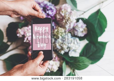 Happy Women's Day Text Sign On Phone Screen In Woman Hands On Background Of Hydrangea Flowers On Rus