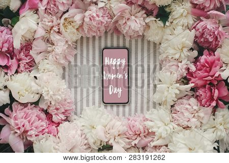 Happy Women's Day Text Sign On Phone Screen And Peonies Frame Flat Lay On Rustic Table Cloth. Stylis