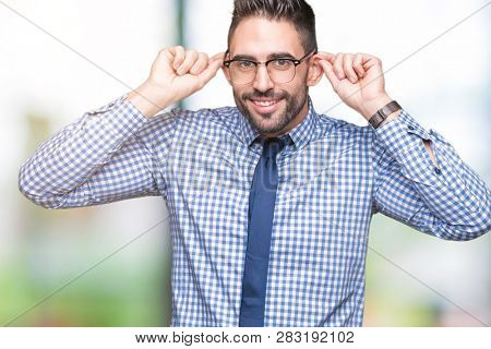 Young business man wearing glasses over isolated background Smiling pulling ears with fingers, funny gesture. Audition problem