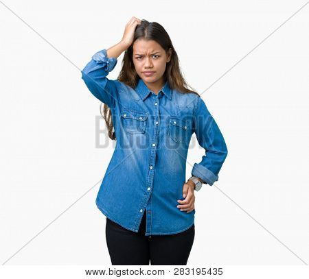 Young beautiful brunette woman wearing blue denim shirt over isolated background confuse and wonder about question. Uncertain with doubt, thinking with hand on head. Pensive concept.