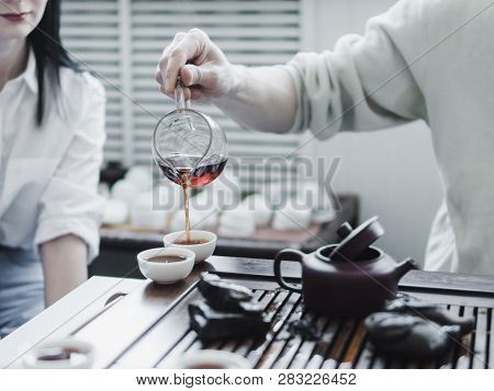 Chinese Tea Ceremony. Master Pouring Puer Tea In Cups. Pu Erh Tea Ceremony.