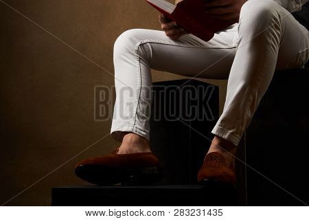 Young Businessman In Casual Clothes Reading A Book While Sitting On Wooden Box
