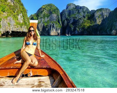 Young Woman Sitting At The Front Of Longtail Boat In Maya Bay On Phi Phi Leh Island, Krabi Province,
