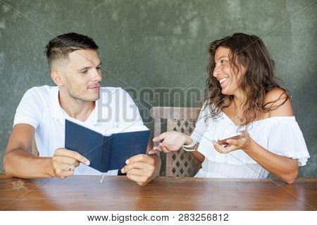 Reading Books Is Better Than Internet Surfing. Young Couple In White Sitting At Table. Man Holding O