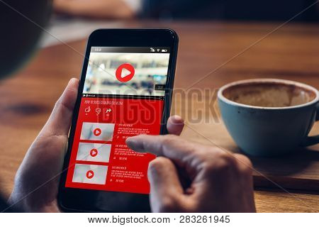 Close Up Woman Hand Holding Mobile Watching Video Online With Advertising On Mobile On Sofa At Home.