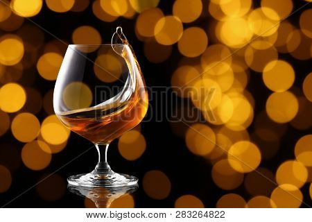 Splash Of Brandy In Snifter Glass On Blurry Lights Background