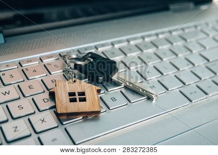 Metallic Key On Key Ring With House Symbol Lying On Laptop Keyboard. Real Estate And Internet Concep