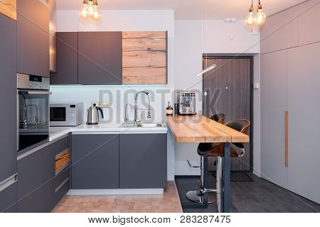 Modern Kitchen Interior With Lights On. Brown Wooden Table And Bar Stools, Coffee Machine. Contempor