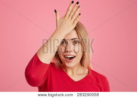 Forgetful Young Woman Keeps Hand On Forehead, Looks With Amazement, Opens Mouth, Dressed In Red Clot
