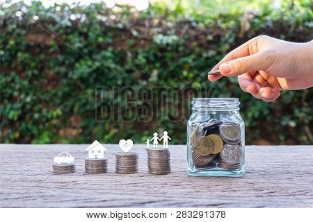 Savings Money For Family Life Concepts. Hand Holding Coin On A Full Money In Glass Jar And Family Me