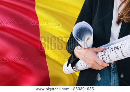Guinean Architect Woman Holding Blueprint Against Guinea Waving Flag Background. Construction And Ar