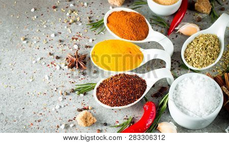 Spices In Wooden Spoon. Herbs. Curry, Saffron, Turmeric, Rosemary, Cinnamon, Garlic, Pepper, Anise O