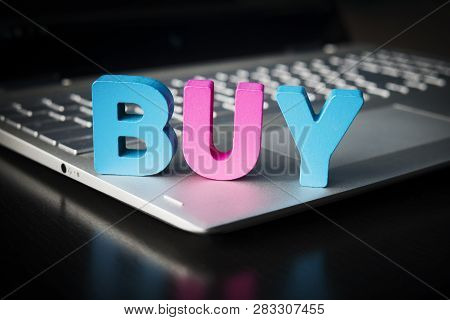 Buy Word On Laptop Bottom At Black Background. Wooden Colorful Letters B, U, Y Set On Opened Noteboo