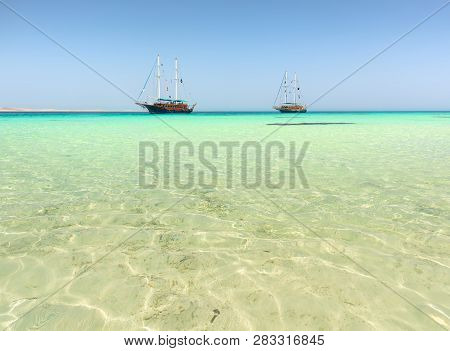 Two Sailboats In Turquoise Sea Under Sunlight