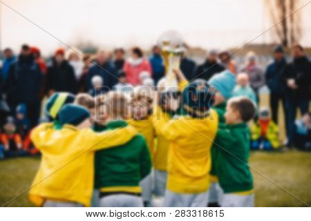 Blurred Background Of Kids Sport Team With Trophy. Kids Celebrating Football Championship. Happy You