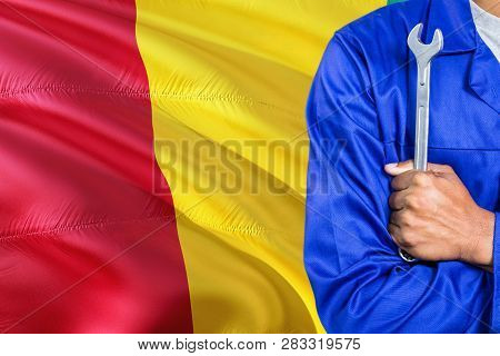 Guinean Mechanic In Blue Uniform Is Holding Wrench Against Waving Guinea Flag Background. Crossed Ar