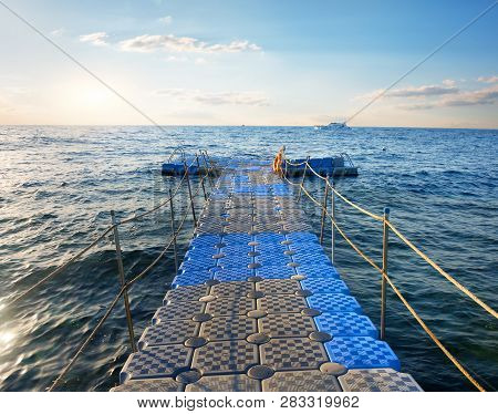 Pontoon With Handrails In The Sea At Sunset