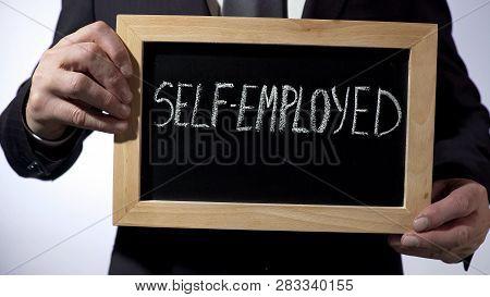 Self-employed Written On Blackboard, Businessman Holding Sign, Business Concept