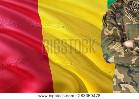 Crossed Arms Guinean Soldier With National Waving Flag On Background - Guinea Military Theme.