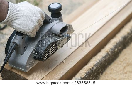 Carpenter working with electric planer on wooden plank in outdoor. Woodworking and craftsmanship concept poster