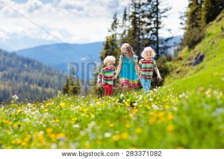 Children Hiking In Alps Mountains. Kids Outdoor.