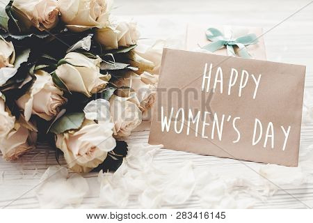 Happy Women's Day Text Sign On Craft Greeting Card And White Roses Bouquet, Gift Box On Wooden Backg