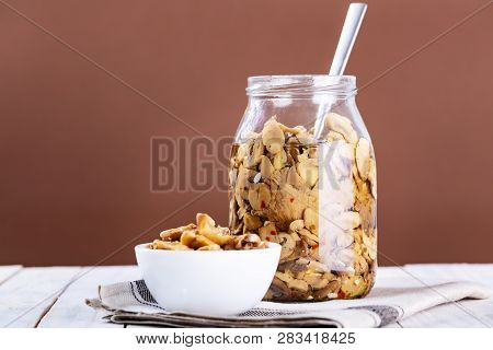 Mushrooms In Oil In A Glass Jar On White Wooden Background.