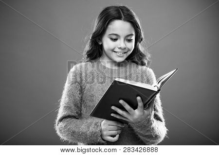 Reading Activities For Kids. Girl Hold Book Read Story Over Orange Background. Child Enjoy Reading B