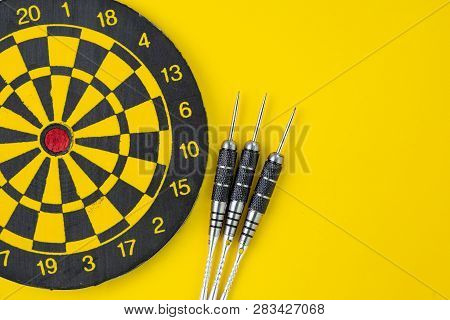 Flat Lay Of Perfect Black Darts With Dartboard On Solid Yellow Background With Copy Space Using As T