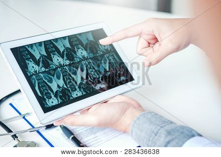 Doctor Consulting With Patient Presenting X-ray Film Results On Digital Tablet Tablet Sitting At Tab
