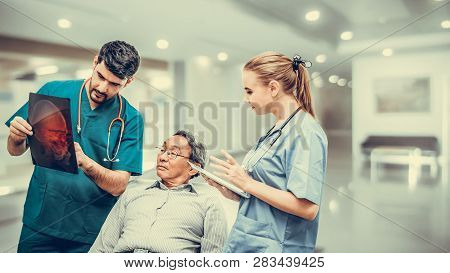 Surgeon Showing Xray Film To Senior Patient Looking At Brain Injuries With Nurse Standing Beside The