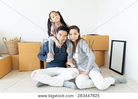 Happy Young Asian Family Moves The Boxes To A New Home And Looking At Camera. Moving Concept.