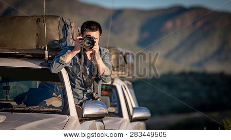 Young Asian Man Traveler And Photographer Sitting On The Car Window Taking Photo On Road Trip In Nam