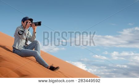 Young Asian Woman Traveler And Photographer Holding Camera Taking Photo While Sitting On Sand Dune I
