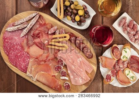 Gourmet Charcuterie. An Assortment Of Sausages And Hams, Deli Meats, Shot From The Top On A Dark Rus