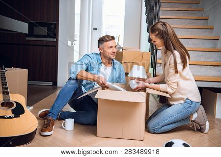Cheerful Husband Looking At Wife Unpacking Box And Holding Lamp In Hands While Sitting On Floor