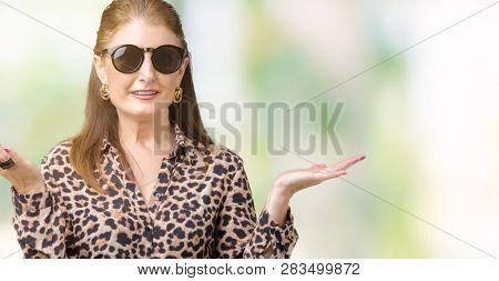 Middle age mature rich woman wearing sunglasses and leopard dress over isolated background clueless and confused expression with arms and hands raised. Doubt concept.