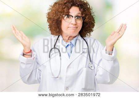 Middle ager senior doctor woman over isolated background clueless and confused expression with arms and hands raised. Doubt concept.