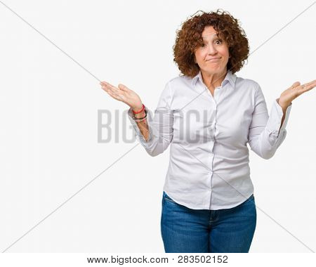 Beautiful middle ager senior businees woman over isolated background clueless and confused expression with arms and hands raised. Doubt concept.