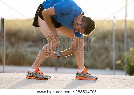 Runner Holding His Knee In Pain After Pulling A Muscle.