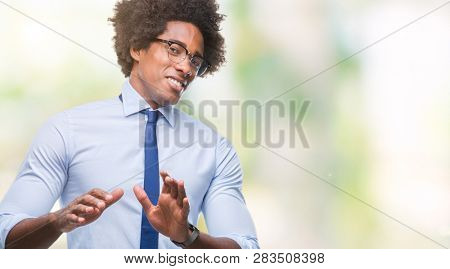 Afro american business man wearing glasses over isolated background disgusted expression, displeased and fearful doing disgust face because aversion reaction. With hands raised. Annoying concept.