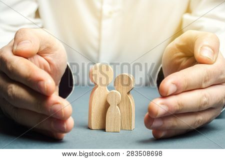 Insurance Agent Holds Hands Near The Family. The Concept Of Insurance Of Family Life And Property. F