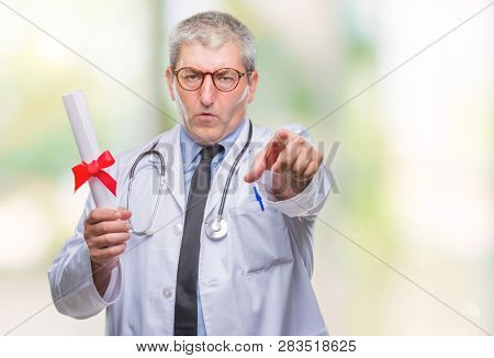 Handsome senior doctor man holding degree paper over isolated background pointing with finger to the camera and to you, hand sign, positive and confident gesture from the front