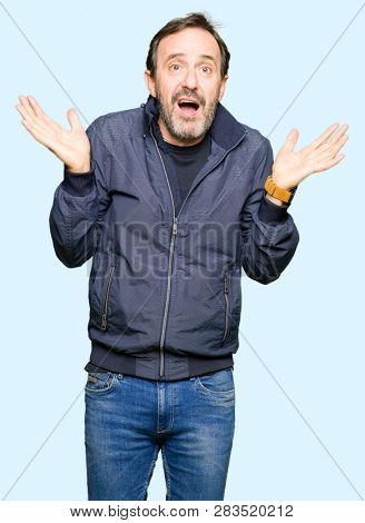 Middle age handsome man wearing a jacket clueless and confused expression with arms and hands raised. Doubt concept.